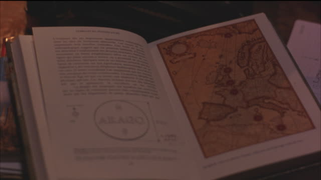 close angle of book opened to picture of map of europe on table. - cartography stock videos & royalty-free footage