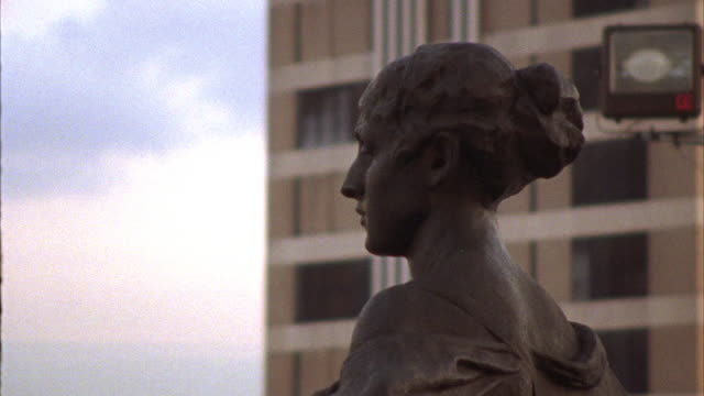 MEDIUM ANGLE, PAN DOWN OF STATUE. STATUE IS LADY JUSTICE SITTING IN CHAIR. OFFICE BUILDING OR SIMILAR IN BG.