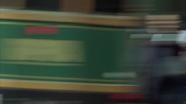 hand held angle of a trolley at a bus stop. several people waiting for it. the camera zooms in and out of the logo on the front. - trolley bus stock videos & royalty-free footage