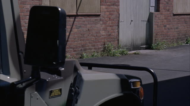 medium angle of front right side of military vehicle or hummer or humvee. see side view mirror and camouflage paint on vehicle. brick building in background with wood boards over windows and locked wooden door. - hummer stock videos & royalty-free footage