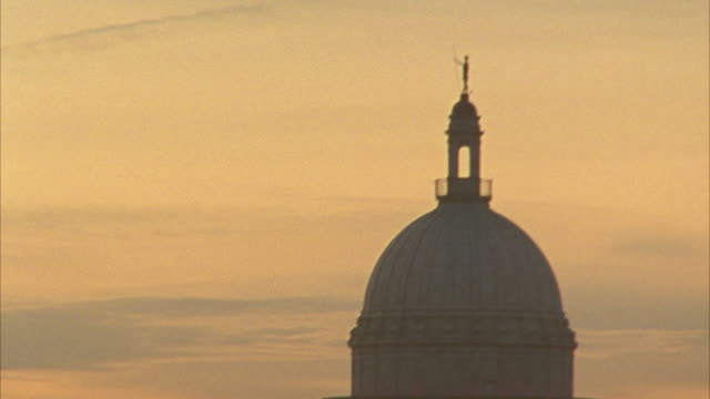 hand held angle moving back and forth from a sunset to the rhode island state house capitol building. government building, domed building. - https点の映像素材/bロール
