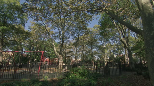 wide angle of swing set in fenced- in playground in mcgolrick park in the greenpoint neighborhood of  brooklyn. zoom in on trees. - greenpoint brooklyn stock videos & royalty-free footage