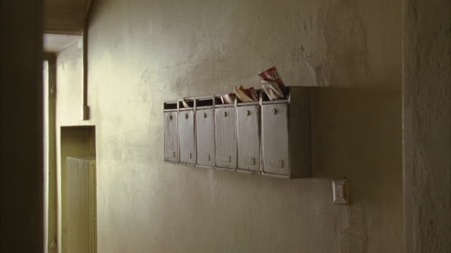 medium angle of mailboxes on wall. mailboxes stuffed with mail. apartment building entryway, hallway, or lobby. radiator, heating element, set into wall, visible in bg. - letterbox stock videos & royalty-free footage