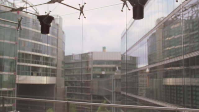 medium angle of windows in konzern-forum building in autostadt complex. pov shot out the window looks out into courtyard with other buildings in autostadt complex. glass windows. track lighting. could be bank or office building. - wolfsburg lower saxony stock videos and b-roll footage