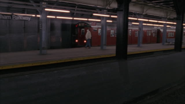 """vídeos de stock e filmes b-roll de medium angle pan left of subway train stopping by """"pelham parkway"""" subway station from right to left. platform in foreground. - 1995"""