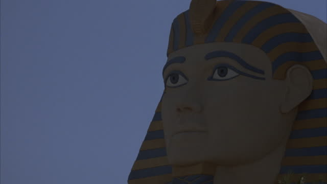 MEDIUM ANGLE OF HEAD OF SPHINX FIGURE FACING LEFT AT LUXOR HOTEL. JET FLIES TO RIGHT IN BOTTOM BACKGROUND.