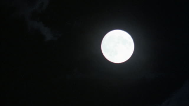 close angle of full moon with light wispy clouds in foreground. camera pans down and to left at end. - wispy stock videos & royalty-free footage