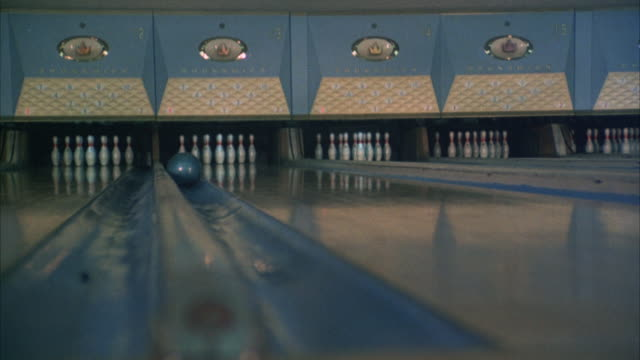 vídeos de stock, filmes e b-roll de medium angle bowling lanes. see bowling ball roll down gutter of one lane and miss bowling pins. gate moves down and resets pins. see bowling ball move opposite in gutter to right. - cancha de jogo de boliche