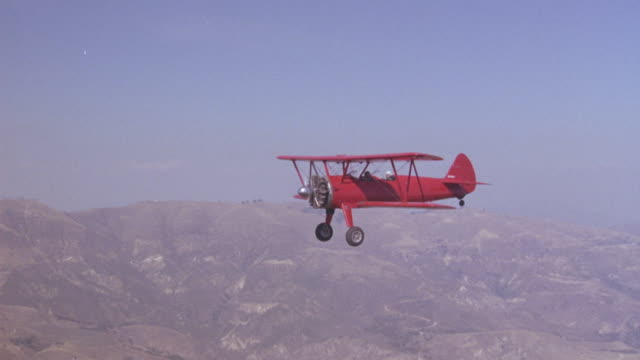 aerial. flying beside red biplane flying above mountains. - biplane stock videos & royalty-free footage
