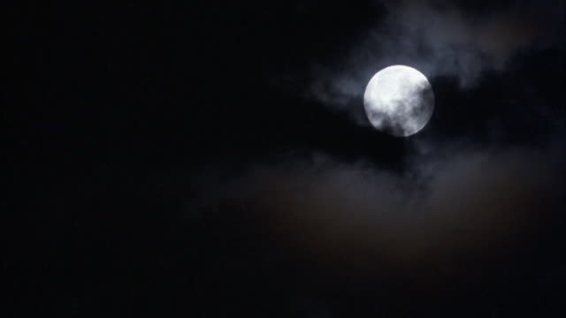 vídeos de stock e filmes b-roll de close angle of full moon in sky. see dark clouds moving across screen from right to left, partially blocking the moon. - lua