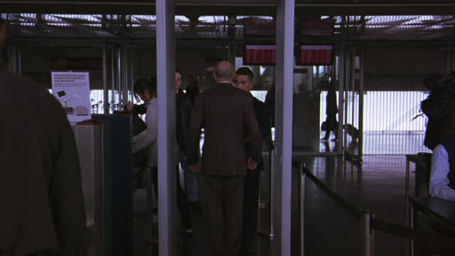 WIDE ANGLE OF ELDERLY MAN WALKING THROUGH METAL DETECTOR AND BEING CHECKED BY SECURITY. COULD BE AT AIRPORT OR TRAIN STATION.
