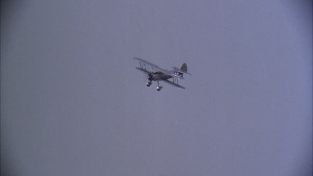 vidéos et rushes de medium angle of biplane flying over mountains and then landing. - biplan