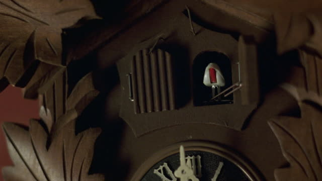 close angle of doors at top of wooden cuckoo clock. see hands of clock at 12:00. see right door open. see white bird with orange beak pop out and rock back and forth. - cuckoo stock videos and b-roll footage