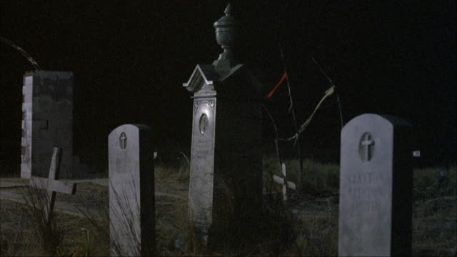 medium angle of spooky graveyard or cemetery with headstones. pov moves in close to headstones. - 礎石点の映像素材/bロール