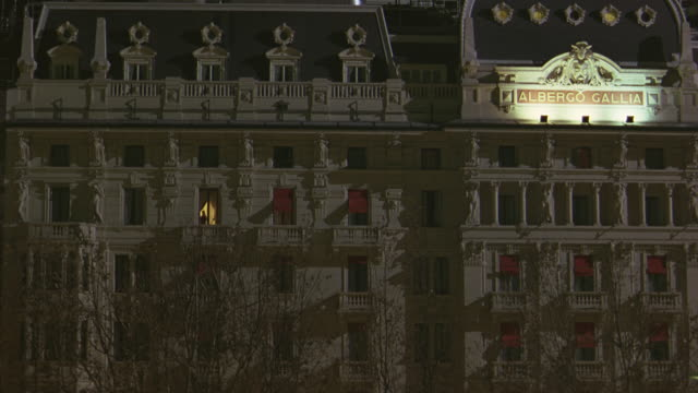"wide angle of hotel le meridien gallia in milan. multi-story building. ""albergo gallia"" sign lit up. - https点の映像素材/bロール"