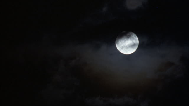 medium angle of full moon with dark wispy clouds passing by in foreground. pans down and left to dark sky. - wispy stock videos & royalty-free footage