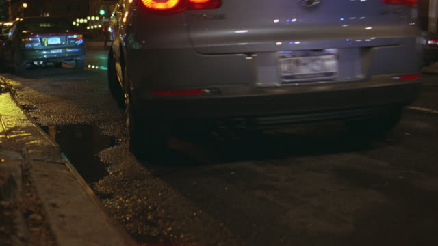 medium angle of rear left bumper and wheels of volkswagen tiguan or other suv parked at the curb of a city street. - volkswagen stock-videos und b-roll-filmmaterial