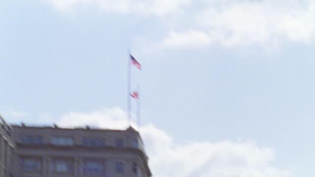vídeos y material grabado en eventos de stock de pan down from top of building with flags. pan down to capitol building twice. see traffic in front of capitol. rapid pan l-r to a dark building. - edificio del capitolio washington dc