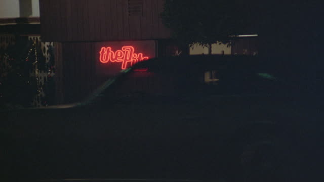 """zoom in and out of neon sign that says """"the pits"""" outside bar. - neon stock videos & royalty-free footage"""