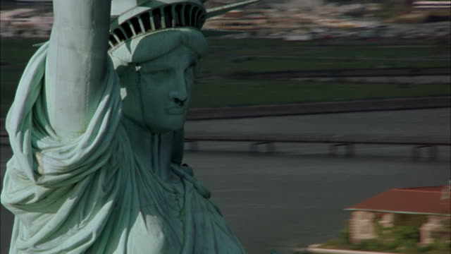 aerial circling statue of liberty, new york harbor. pans down to the stone base of statue with tourists on observation deck. - 2001 stock-videos und b-roll-filmmaterial
