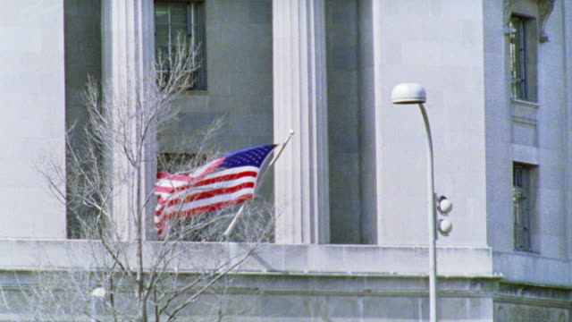 stockvideo's en b-roll-footage met zoom in on american flag handing on side of concrete building, waving in the wind. tree with bare branches in fg. - bare tree