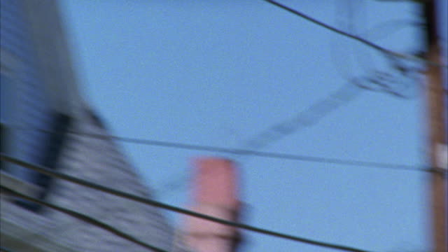 HAND HELD ANGLE OF AN FLAG FLYING BEHIND ELECTRICAL WIRES WITH A CLAPBOARD HOUSE IN THE BACKGROUND.  PROBABLY AN IRISH FLAG WITH A FAMILY CREST. THE CAMERA PANS TO THE AMERICAN FLAG AND DOWN TO A YARD SALE BELOW.