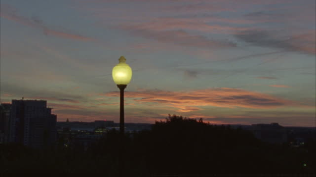 hand held angle from a sunset to lamp post to the rhode island state house capitol building. government building, domed building. - https stock videos & royalty-free footage