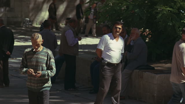 wide angle of townsfolk, townspeople  in courtyard, town square or park. men. - courtyard stock videos and b-roll footage
