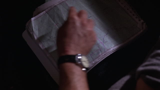 close angle of map on lap of woman in car shows man and woman's hands pointing to roads on map as if arguing about directions. map shows angeles national forest. - angeles national forest stock videos and b-roll footage