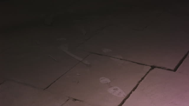 CLOSE ANGLE OF FOOTPRINTS ON DUSTY CEMENT OR CONCRETE FLOOR. FOOTPRINTS COULD BE FROM BOOTS OR MEN'S DRESS SHOES.