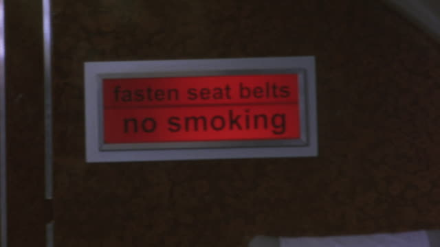 "close angle of red ""fasten seat belts no smoking"" sign on airplane wall. - rules stock videos & royalty-free footage"