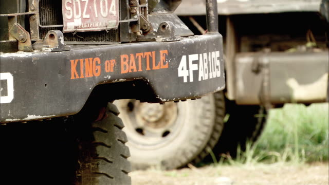 medium angle of military vehicle or jeep bumper, license plate, 'king of battle' printed in orange. other trucks in background. - number plate stock videos & royalty-free footage