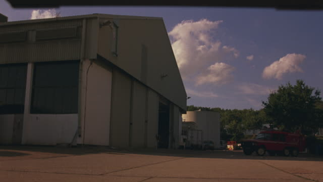 wide angle of airport hangar. trees in background and red suv parked to right. could be used as a small airport in the countryside. - hangar stock-videos und b-roll-filmmaterial