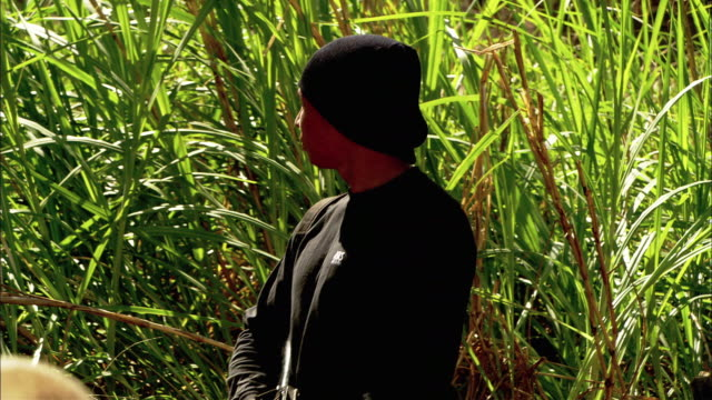 close angle of three gunmen or rebels or insurgents in a field of tall grass. two insurgents walk out of frame. third rebel paces back and forth holding a machine gun. he wears a black hat and black shirt. - schwarzes hemd stock-videos und b-roll-filmmaterial