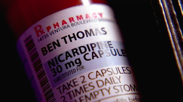 close angle of label on prescription drugs bottle. nicardipine medication used to treat high blood pressure. series. could be located in bathroom, bedroom or kitchen. - pill bottle stock videos & royalty-free footage
