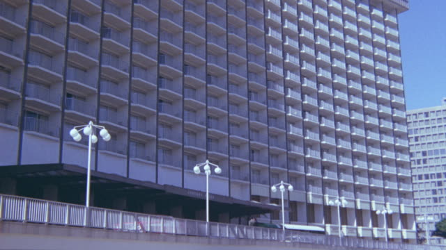 medium angle of los angeles building, century plaza hotel in century city. looks like hotel or apartment building. shot zooms in on building and settles on one hotel room balcony/patio. - 1975 stock videos and b-roll footage