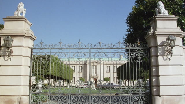 MEDIUM ANGLE ESTABLISH OF BLACK IRON GATE BETWEEN TWO STONE PILLARS.  SEE TWO STORY BUILDING WITH RECTANGULAR WINDOWS BEHIND GATE.