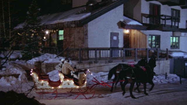 pan left to right of horse drawn carriage decorated with christmas lights traveling through ski resort. man and woman, couple, in front of carriage. drives past hotel, motel or ski lodge. snow. - ski lodge stock videos & royalty-free footage