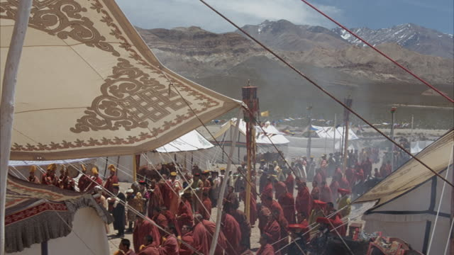 medium angle of tibetan tapestry billowing in wind. see buddha symbol at top flanked by symbols of animals and white mountains at bottom of tapestry with colorful borders. - medium group of animals stock-videos und b-roll-filmmaterial