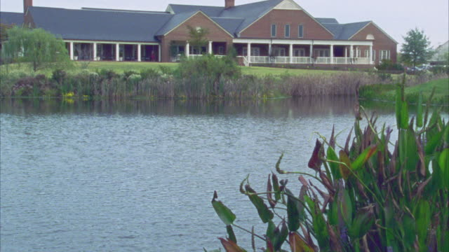vídeos de stock e filmes b-roll de wide angle of lake or pond surrounded by grasses and reeds with sprawling two-story brick building with porch. - comunidade de aposentados