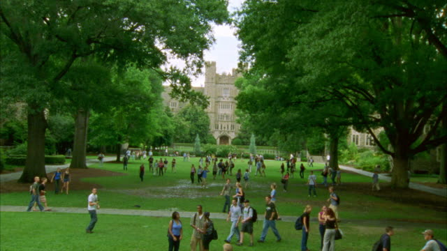 wide angle of people, college students walking through courtyard or quad with grass and trees on college, university or ivy league campus. - ivy league university stock videos and b-roll footage