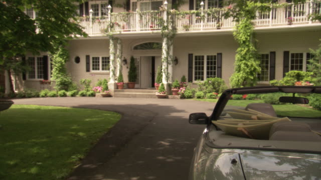 medium angle of front of large house, could be estate or mansion. see house, decorated with hanging plants, ferns, and flowers, in tidewater architecture style. - driveway stock videos & royalty-free footage