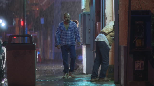 WIDE ANGLE OF MAN PEDESTRIAN WALKING DOWN SIDEWALK IN DOWNTOWN URBAN AREA. SEE RAIN FALLING. SEE MAN APPROACH SECOND MAN STANDING AT OUTSIDE COUNTER OF STORE OR SHOP OR RESTAURANT.