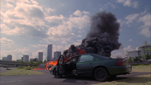 medium angle of stunt man sitting in green car, could be mercury or ford. see black navigator explode. see stunt man jump out of his parked car and fall to ground from explosion impact. - stunt stock-videos und b-roll-filmmaterial