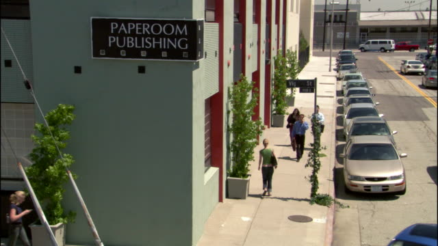 """medium angle of """"paperoom publishing"""" two story teal office building on corner of street. see cars parallel parked on side of building. - zweistöckiges bauwerk stock-videos und b-roll-filmmaterial"""