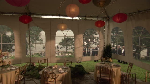 medium angle of tented party area. see red and white hanging lights or lanterns. see empty round tables with plated settings. - tent stock videos & royalty-free footage