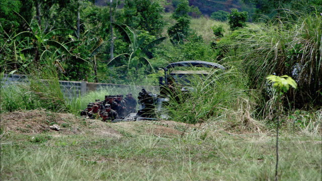 wide angle of military combat in a grassy field. two small explosions fire and several soldiers fall dead. smoke. - tarnung stock-videos und b-roll-filmmaterial