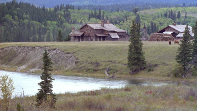 medium angle of two large wood cabins on large expanse of grassy land, fir trees in background, river in foreground. - ranch home stock videos & royalty-free footage
