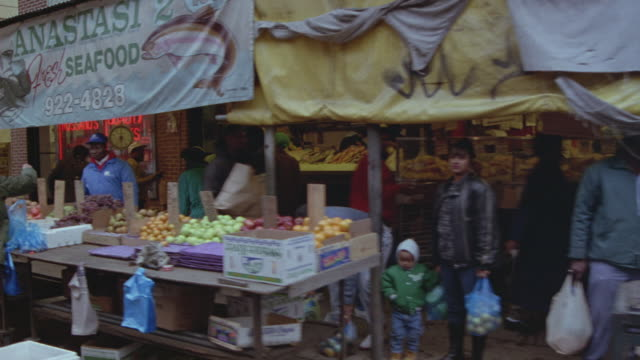 medium angle market area and shops, see people waving toward pov. passenger pov, right to left see covered tables of fruits, vegetables, seafood. - philadelphia pennsylvania video stock e b–roll