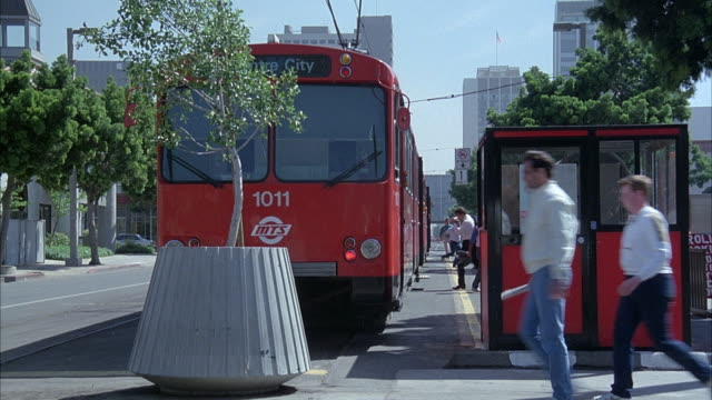 medium angle of red trolley or train stopped in city street at train station. see doors open and people exit trolley on right. - push cart stock videos & royalty-free footage